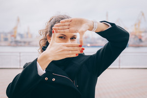 Young woman makes a frame of fingers against the backdrop of a seaport