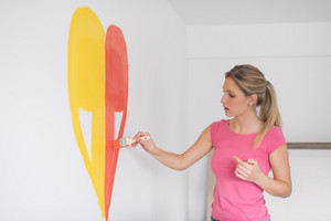 Young woman painting a heart on the wall while doing repair at home.