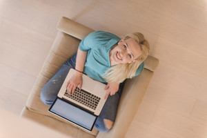 Young woman using her laptop computer in her luxury modern home top view