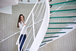young woman walking on spiral stairs in modern home indoors