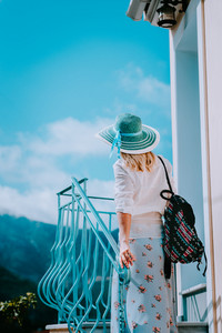 Young woman wearing summer clothes and straw hat going up stairs on sunny day. Vacation holidays in Europe