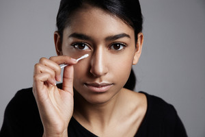 young woman with a cotton stick correcting a makeup