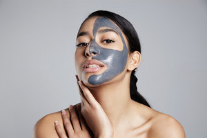 young woman with a facial mask in grey towel Clay grey active caracoal mask