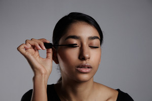 young woman with closed eyes and mascara brush close to them