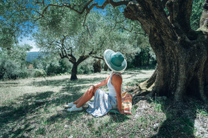 Young woman with straw sun hat under an olive tree on a background of idyllic Mediterranean landscape. Olive forest, fairy tale, relaxing, summertime, Greece