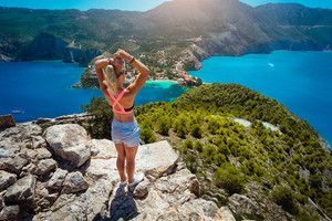 Young women enjoying view to Assos village Kefalonia from top castle. Beautiful blue colored bay lagoon underneath surrounded by pine and cypress trees. Neck of land connect mainland. Greece
