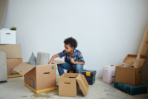 Youngster unpacking carton-boxes in new flat
