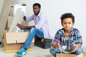Youngster with bowl and his father unpacking box on background