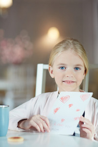 Youthful child with greeting card for her mother