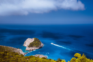 Zakynthos fantastic coastal view with white cliff. White tourist ship sailing full speed on open azure sea water under beautiful cloudscape