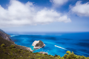 Zante fantastic coastal view with white cliff and azure sea water. White tourist ship sailing full speed on open water