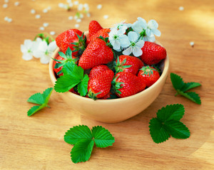 Strawberries in a bowl on wood table