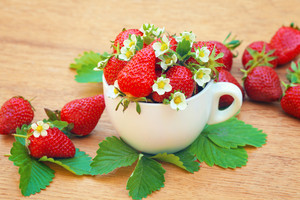 Strawberries in a cup on wooden table