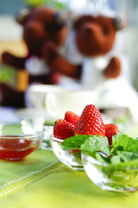 strawberries in the bowl with green fabric