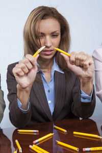 Stressed people breaking pencils in office