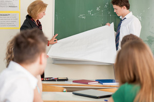 Student and teacher holding a white banner in front of a blackboard