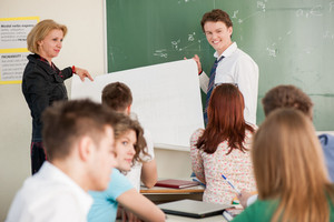 Student and teacher holding a white panel in front of a blackboard