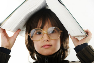 Student child with a book and glasses over his head isolated over white background
