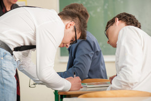 Student helps his colleague in a classroom