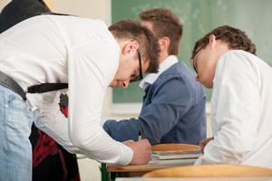 Student in a schoolroom writing in a copybook while his colleague watches