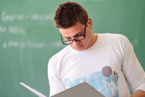 Student in a white shirt reading a copybook