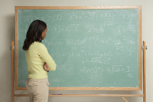 Student standing in front of chalkboard