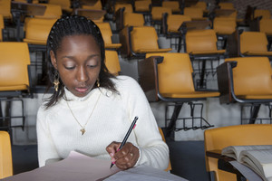 Student taking notes in classroom
