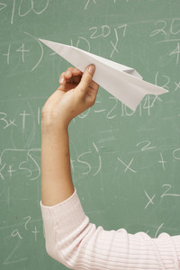 Student throwing paper airplane in classroom