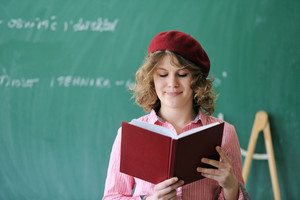 Student with a french cap reading a book in a classroom