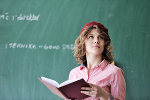 Student with a red french cap thinking in front of a chalkboard