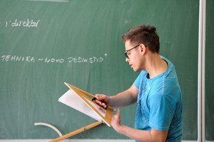 Student with geometry set in front of blackboard