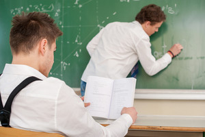 Student writing on a blackboard in a classroom while his colleague is reading