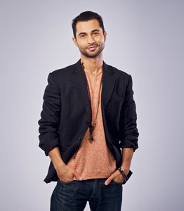 Studio portrait of a confident guy looking and smiling at you