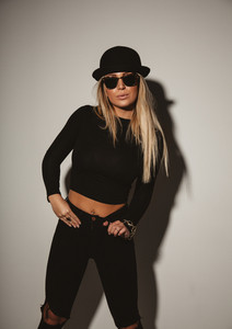 Studio shot fashionable young woman wearing sunglasses and hat looking at camera. Young blond woman posing in casual wear.