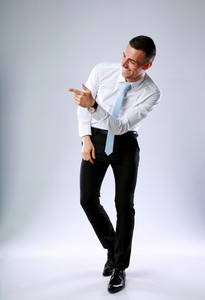 Studio shot of a funny businessman pointing at something on gray background