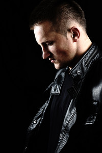 Stylish fashion young Man portrait with leather jacket on black background