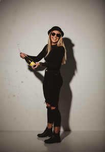 Stylish young woman celebrating with champagne. Studio shot of teenage girl in party with a bottle of champagne.