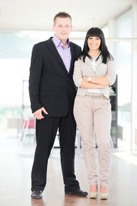 Successful business couple looking at camera standing in office