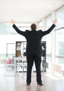 Successful businessman alone rising arms in excitement at office