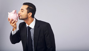 Successful businessman kissing a piggy bank while holding it