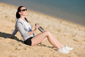Summer active woman sit on beach sunset in fitness outfit