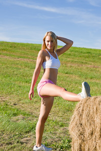 Summer active woman stretching on bales in fitness outfit