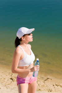 Summer beach active woman relax after jogging in fitness outfit