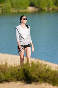 Summer beach active woman walk on seaside in fitness outfit