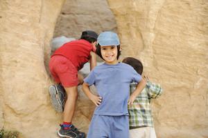 Summer tourist vacation, children playing around the little cave