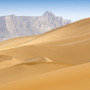 Sunlit, desert sand dunes and distant rocky cliffs