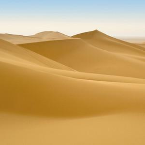 Sunlit desert sand dunes at dawn