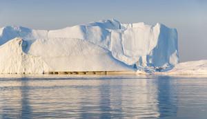 Sunlit, dirt-streaked iceberg in calm waters