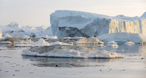 Sunlit, dirt-streaked icebergs and ice floes in icy waters