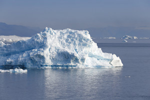 Sunlit iceberg against a foggy sky